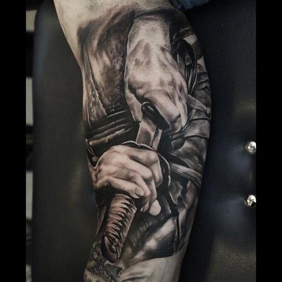 A black and grey tattoo piece of a katana being drawn by artist Domantas Parvainis. | Intenze ink