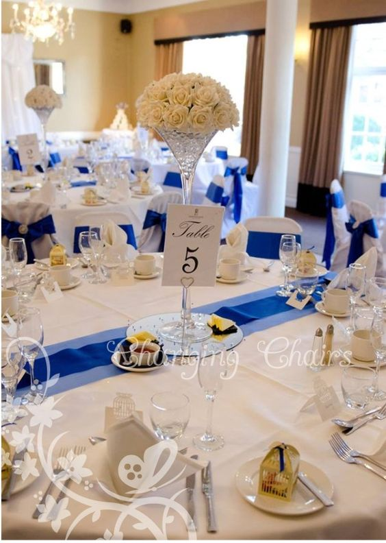 Changing Chairs wedding table centres just ivory roses in tall martini vases so chic !