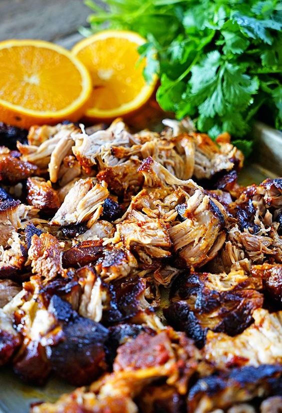 ... pork is slow roasted in cumin, oregano, and chile marinade, then