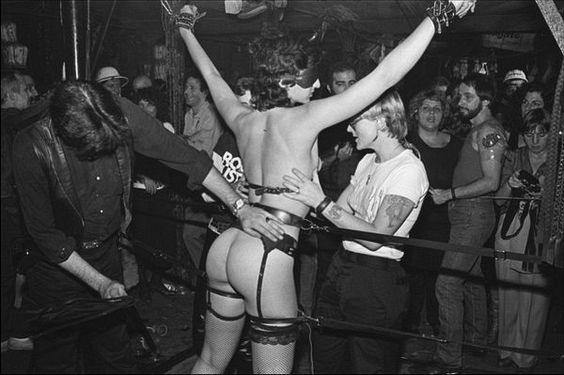 Half-naked woman in bondage, surrounded by crowd