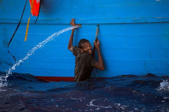 A man holds himself on the side of a boat after jumping into the sea from a crowded wooden boat during a rescue operation at the Mediterranean sea on Aug. 29. Sabratha, Libya Rettungsaktion im Mittelmeer. (29. August)
