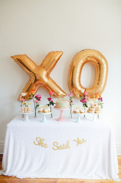 "Light pink + gold bridal shower dessert display idea - donuts + cupcakes + cake displayed on white table linen with gold ""XO"" balloons + ""She said yes"" gold banner - design by @bashandcoparty {Scarlet O'Neill}:"