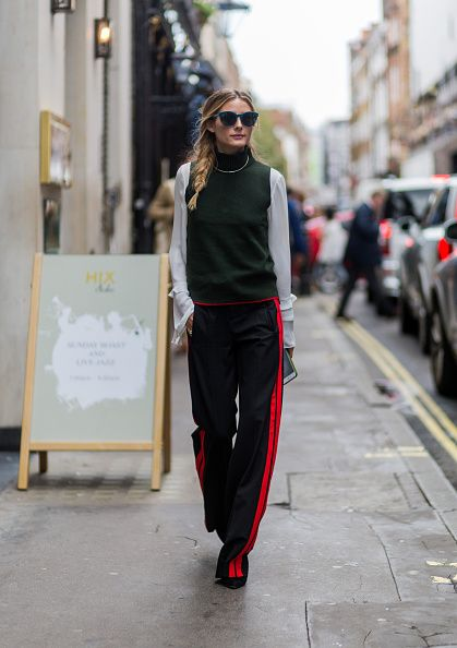 Olivia Palermo wearing sunglasses a green sleeveless jumper white blouse black…: