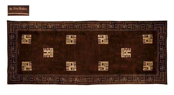 IVAN DA SILVA BRUHNS (1881-1980) GRAND TAPIS DE LAINE, VERS 1925-1930 De forme rectangulaire, de couleur chocolat, à décor d'une frise de grecques sur le pourtour et de motifs géométriques beiges 940 x 410 cm. (370 1/8 x 161 3/8 in.) Signé da silva bruhns et portant le monogramme de la Manufacture de Savigny MS sur la bordure