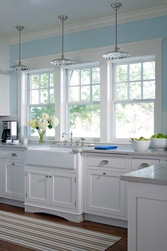 white farm sink, kitchen windows, white cabinets, light blue walls