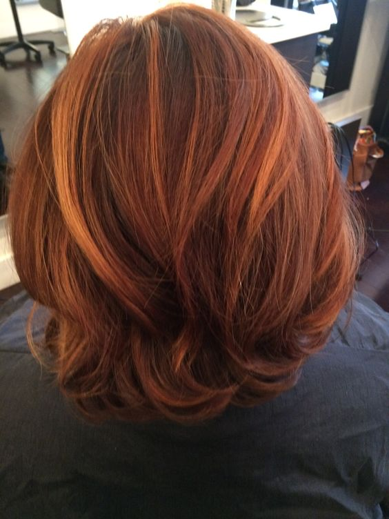 Multi-dementional auburn red with honey highlights.  Hair by Claudette