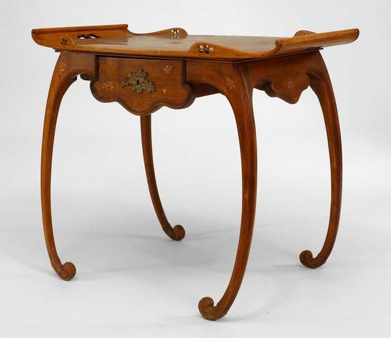 French art nouveau walnut serving table with inlaid floral design by Émile Gallé. From here.