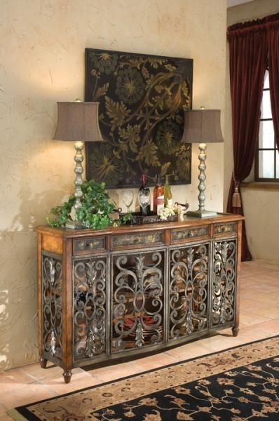 This grand console features scrolled iron doors and a leather top with an etched brass insert.    Complete with four doors, four drawers, and one shelf. $2,100