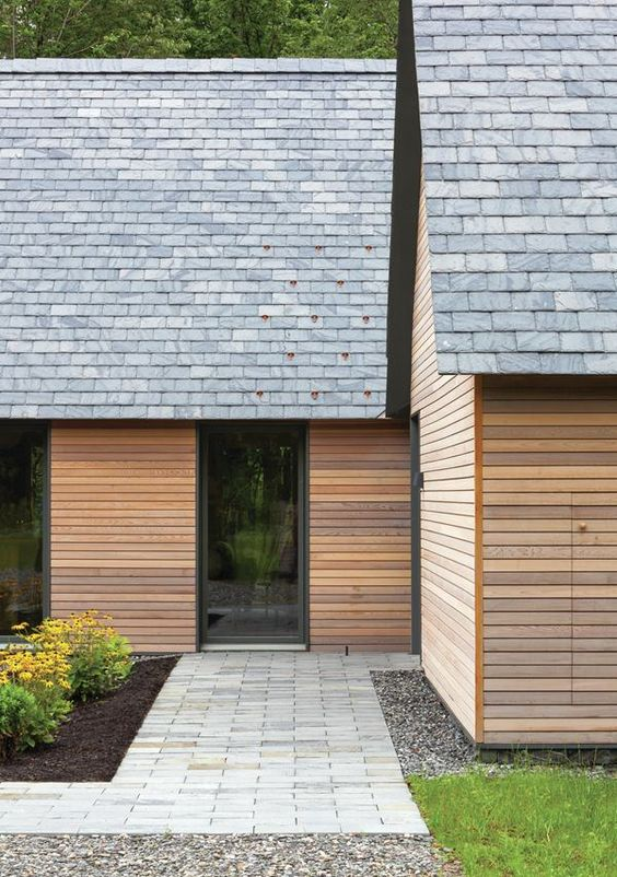 Each cabin is clad in stained cedar siding, and topped with a pitched roof lined in shingles, in the Heathermoor colorway, from Vermont Structural Slate Co.