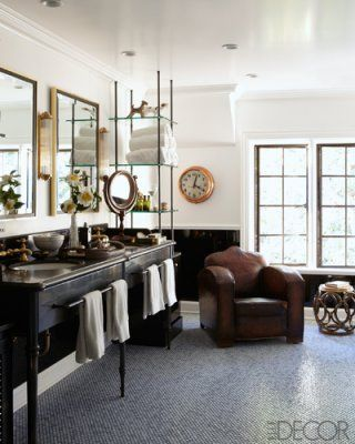 The master bath vanity is custom made, and the brass stool and English club chair are vintage; the clock once hung in an Associated Press newsroom, and the floor is paved in glass tiles by Waterworks.