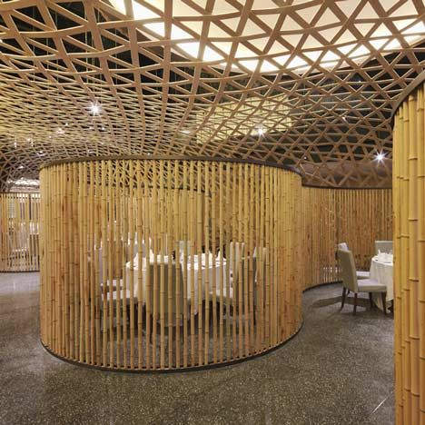 A woven net of bamboo creates a curved suspended ceiling inside this restaurant.:
