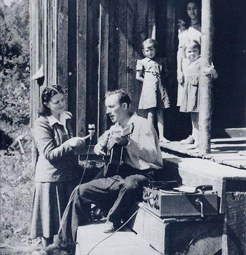 Anne Warner recording Frank Proffitt, who sings and plays the guitar, as children look on