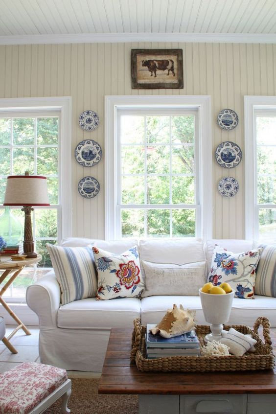 Traditional decor and country cottage style sun room with red, white, blue. Beadboard walls and casual feel with blue and white plates hung on wall.