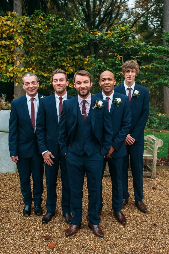Groomsmen in three piece navy suits with maroon ties - Image by Hannah May - Autumnal rustic themed wedding with Navy, Maroon & Gold Colour Scheme. Bride in Lace Wedding Dress & Bridesmaids in beaded Navy dresses. Groom wears a suit from Next & patterned shirt from Ted Baker.