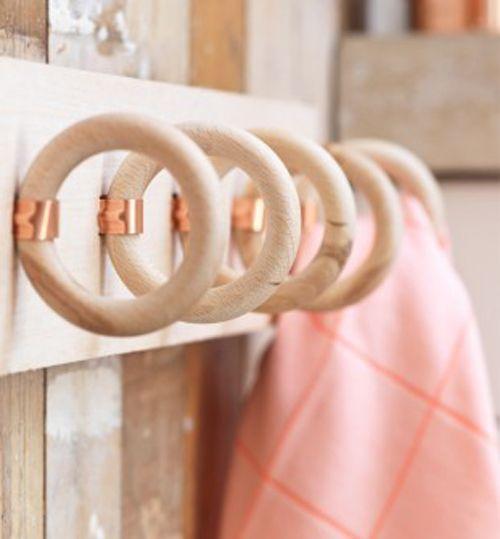 Portasciugamani con anelli delle tende   Avete smontato un vecchio bastone per la tenda e non sapete cosa farne? Potete utilizzare gli anelli di legno come portasciugamani in bagno! Ecco cosa vi serve 5 anelli per tende in legno 5 fascette da idraulico Vernice color rame (opzionale) Una tavola di legno spessa 10 cm misure 5410 cm Taglierina Come procedere Verniciate le fascette con la vernice color rame se lo desiderate. Create con la taglierina 5 insenature (13x10mm) dove inserire le…