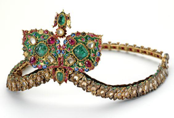 GOLD,ᅠCABOCHONᅠ EMERALD,ᅠ CABOCHONᅠRUBY,ᅠDIAMOND,ᅠ WHITEᅠSAPPHIREᅠANDᅠENAMELᅠ DIADEM,ᅠ 19THᅠCENTURY.  Aᅠcombinationᅠofᅠtwo styles,ᅠtheᅠdiademᅠdecoratedᅠwith table-cutᅠwhiteᅠsapphiresᅠand appliedᅠenamelᅠdepictingᅠaᅠfloralᅠ motifᅠofᅠIndianᅠorigin,ᅠtheᅠcenter sectionᅠofᅠQajarᅠstyleᅠappliedᅠwithᅠ enamelᅠflowers,ᅠtheᅠreverse depictingᅠdancingᅠgirls. ᅠTheᅠfront setᅠwith cabochon emeralds,ᅠ cabochonᅠrubiesᅠandᅠrose-cutᅠandᅠ table-cutᅠ diamonds. (Sotheby's)