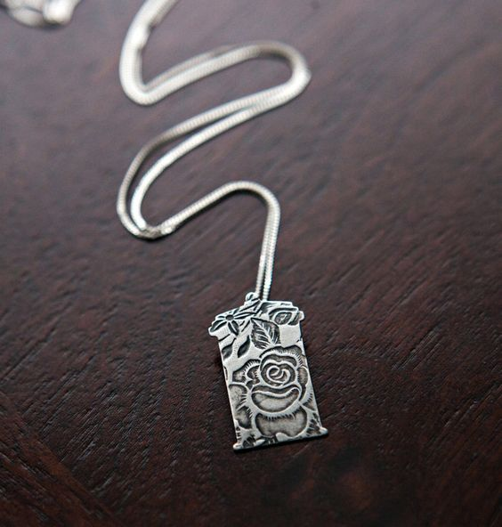 Inspired by the iconic time traveling police box, this rose patterned TARDIS necklace pays tribute to the Doctor and Rose Tyler's relationship.