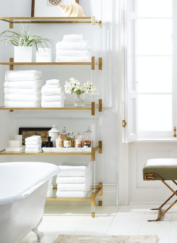 Beautiful all-white bathroom with bright brass and gleaming gold accents.