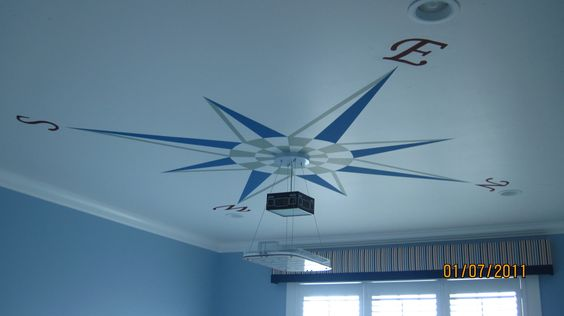Compass painted on ceiling for map themed room