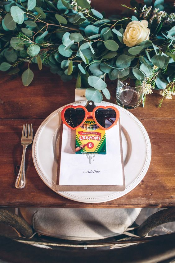 Keep it simple on the kids table. A pack of crayons, a clipboard of fresh paper, and pair of cute shades are all you need to keep little ones content throughout the event.