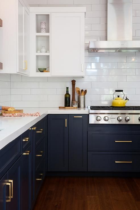 White and blue kitchen features white upper cabinets and navy blue lower cabinets adorned with aged brass pulls paired with white quartz countertops that resemble marble and a white stacked tile backsplash.: