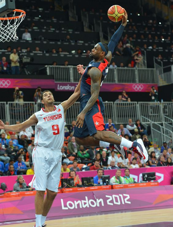 USA's Lebron James, right, dunks over Tunisia's Mohamed Hadidane, left, during the first half of a preliminary men's basketball game at the 2012 Summer Olympics, Tuesday, 31 July 2012 in London    (photo credit: Eric Gay of the Associated Press)