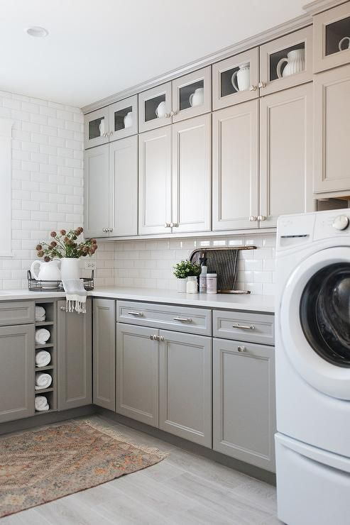 White And Light Gray Laundry Is Equipped With A White Front Loading Washer And Dryer Placed Beneath Grey Laundry Rooms Wall Decor Laundry Laundry Room Storage