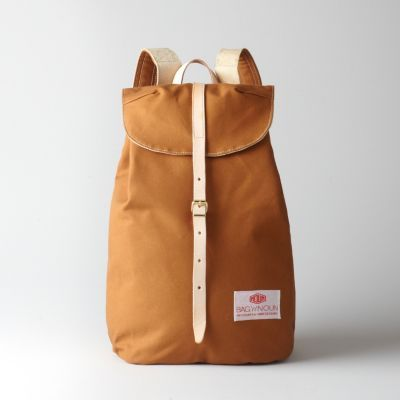 """Japanese made, quality constructed utility bags in clean, classic designs. Duck canvas rucksack with drawstring tie top and leather strap and buckle closure, Canavs shoulder straps with all brass hardware. Single main compartment with top cover flap. Hidden flat pocket with zipper underneath the top cover.    • two total pockets  • signature patch logo  • dimensions: 15.5""""L 10.5""""w 7.5""""d  • 100% cotton canvas  • wipe clean with damp cloth  • made in Japan"""