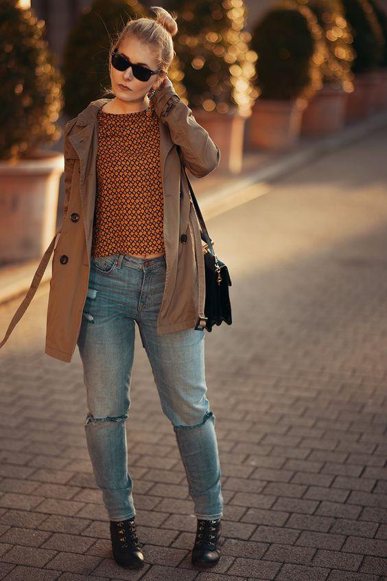 Brauner Trenchoat mit orangefarbenem Retroshirt und blauer Jeans im used look