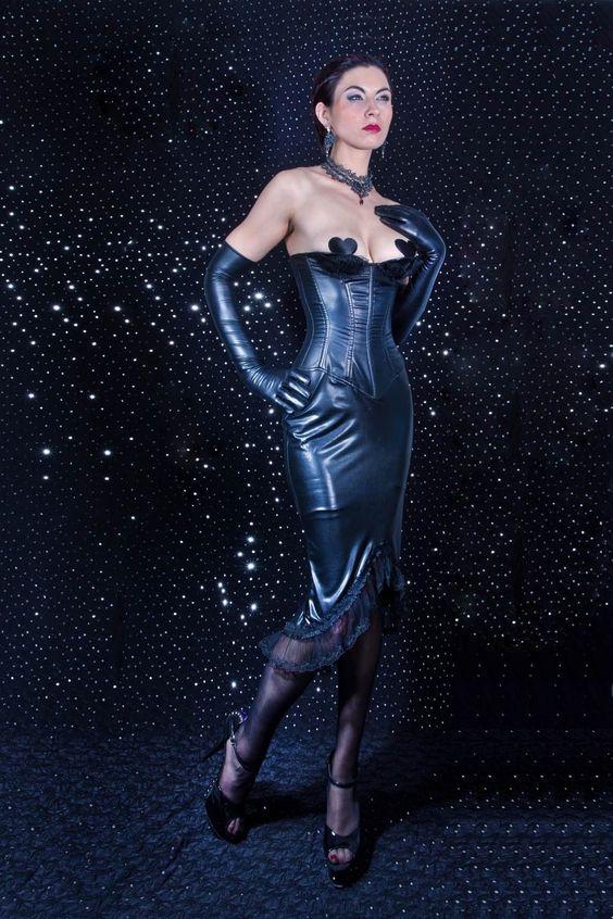 Une robe qui dessine les courbes féminines et donne une allure de pin-up. Tissu laqué noir. Coupe corset sur le haut à demi-bonnets, laissant une partie de la poitrine à découvert. Laçage divin au dos. Le bas offre une belle longueur, à la coupe droite et asymétrique sur le bas agrémenté de tulle transparente.