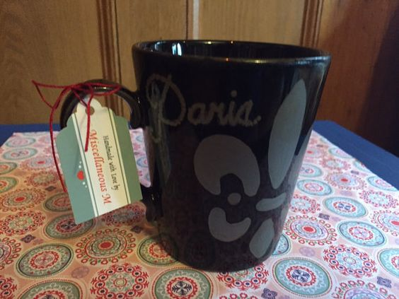 """Handpainted blacksharpie art mug, the word """"Paris"""" in cursive lettering and a Silver Fleur de lis. Black, shiny finish mug painted with oil based ceramic markers. Stored in a smoke free environment. Food and drink safe. 4"""" tall, 3.5"""" diameter opening.  #miscellaneousm"""