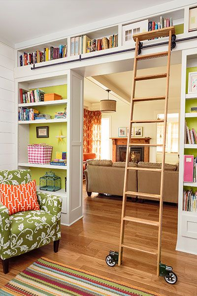 Bookcases by designer Bret Franks are arranged to form a passageway and united with flat trim to create a mini library, complete with a rolling ladder that beckons young readers to hunt for a good book on the topmost shelves.: