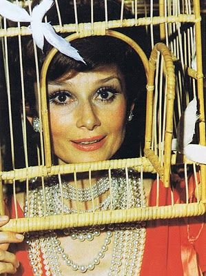 Audrey Hepburn wearing a Magritte bird cage at the diner des testes surrealistes, 1972