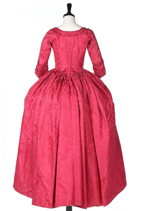 Rear view, robe à l'Anglaise, ca. 1770, fabric: late 1720s, early 1730s. Crimson silk damask, front skirt edging an dangular cuffs edged in pinked, scalloped furbelows, ivory silk lining.