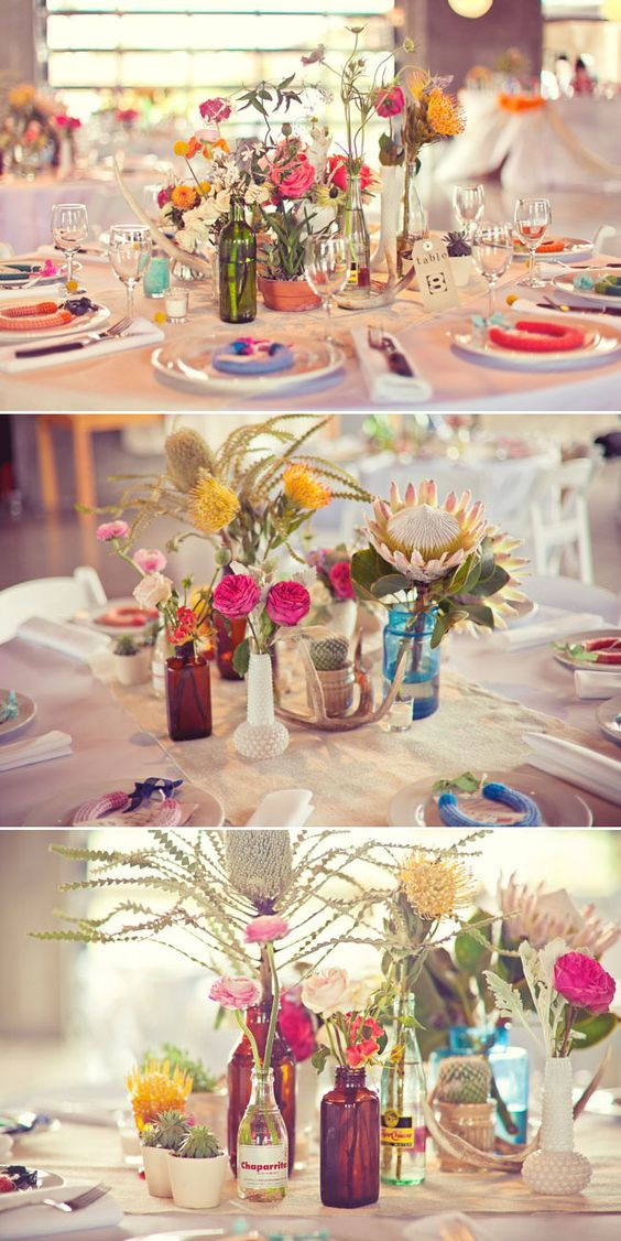 """Other tables will havea  a mix of vintage vases, bottles, and bud vases, (7 total) some with a planted cactus or succulent and the rest with a mix of green and purple foliages, pepperberry, purple stock flower, burgundy scabiosa, pink lisianthus, peach """"finesse"""" garden style roses, yellow craspedia, pink astilbe, and fuchsia peonies; anters and  gold mercury glass votives will be tucked in around the vases"""