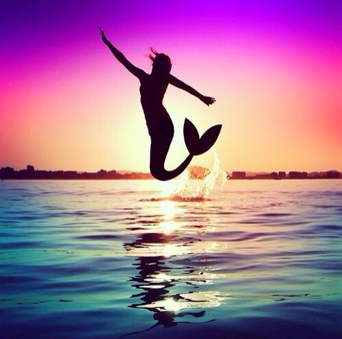 Silhouette of a mermaid jumping out of the water