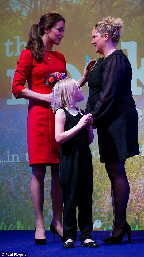 Brave: The Duchess of Cambridge speaks to the mother of Aimee Benton, seven, who presented her with a posy:
