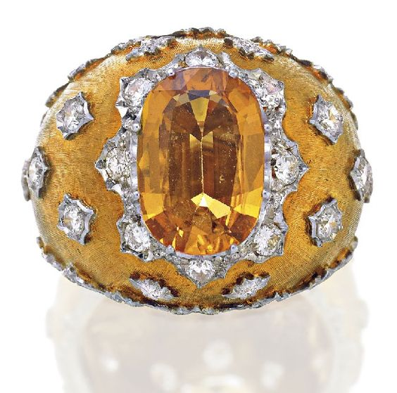 YELLOW SAPPHIRE AND DIAMOND RING, BUCCELLATI.Of bombé style centring an oval cut sapphire weighing approximately 3.00 carats within a round brilliant cut diamond set sculptured surround, to a textured mount applied with diamond highlights, the diamonds together weighing approximately 0.70 carats, mounted in 18ct gold, signed Buccellati,