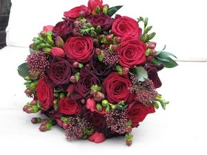 Deep red winter wedding bouquet with roses, hypericum berries and glossy green foliage. Design by www.emmalappinflowers.com