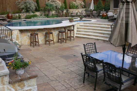 Here's a unique stone deck that actually provides you with a bar right off the side of the pool. You're going to have a whole lot of fun with this one and you'll be able to get plenty of chairs nearby too.