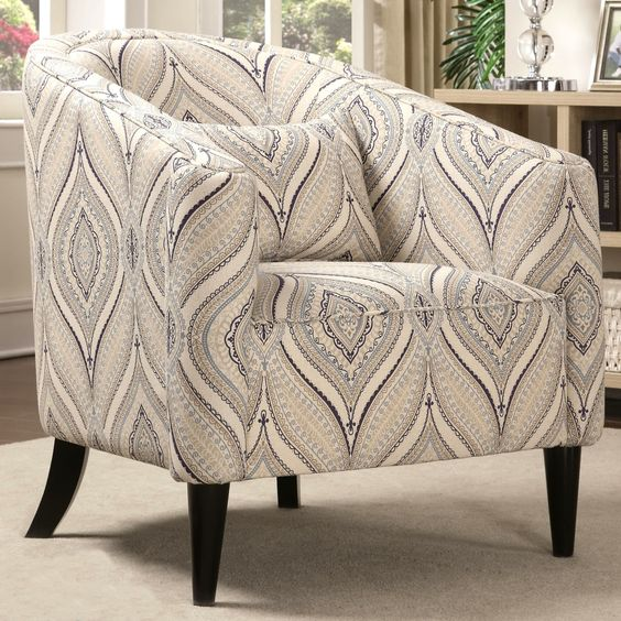 Features a curved back that slopes down to create arms, plush cushion seat upholstered in a multi-color soft linen-like printed fabric and a small accent pillow for additional lumbar support, slighty flared wood legs finished in a black color.