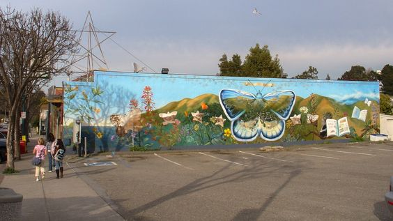 This mural narrates the history of the small town of Brisbane, California. It features the native flora of nearby San Bruno Mountain, and a series of smaller pictures within it show the transformation of the land and communities there over time.