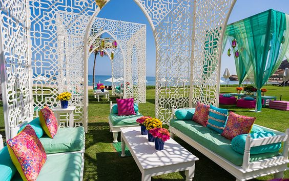 Moroccan-inspired, white 'jaali' cabanas interspersed with low tables and large cushions for Anusha and Dhrumil's mehendi decor