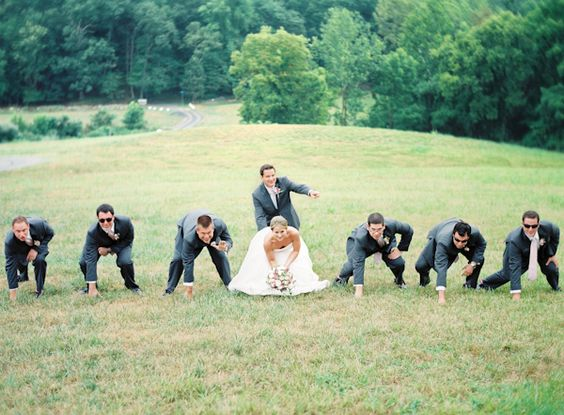 Wedding photo football pose :: - I am a big football fan and I really like this unique pose. It's a good way to show everyone off and have some fun. Even the guests could be a part of this one! I'm not sure how much open space there is on the lawn of our venue, but something tells me we could make this work.