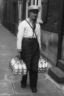 A milkman delivering bottles of milk during his morning round. The sight and sound most people woke up to in the UK for generations now in danger of vanishing completely due to householders buying their milk and bread in blimin supermarkets.If you can, support your Milkman!