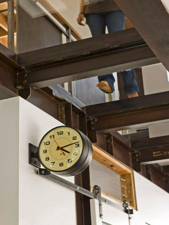 Designer's Notes  A raw steel and glass catwalk provides access to the second floor bedrooms of this industrial modern home. A vintage clock, salvaged from a French railway station, was an amazing find and is one of the coolest vintage pieces we ran across during the project.