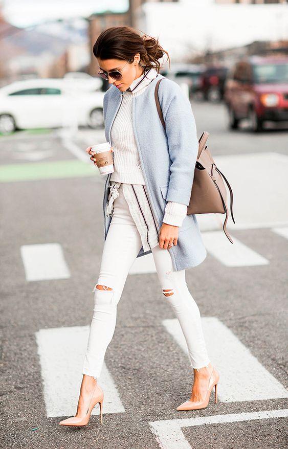Christine Andrew atravessa a rua posando para foto de street style usando camisa com listras, sueter branco, casaco azul serenity, calça jeans branca skinny destroyed e scarpin nude: