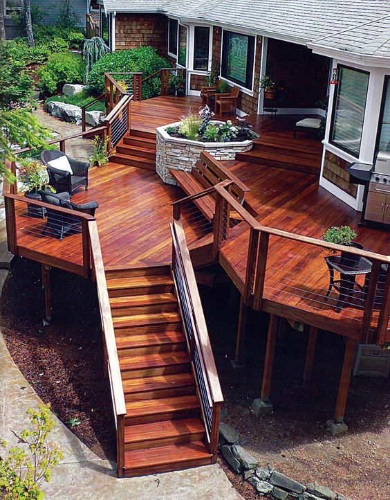 Multi level deck with a stone planter as the focal point for Multi level patio designs