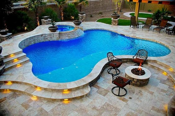 Freeform pool with raised spa with spillover, travertine decking with lighted steps, and fire pit.