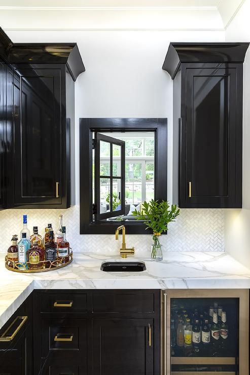 Glossy Black Wet Bar Cabinets Accent Brass Pulls Contrasted By Honed White And Gray Marble Countertops Fitted With A Cur Wet Bar Cabinets Wet Bars Wet Bar Sink